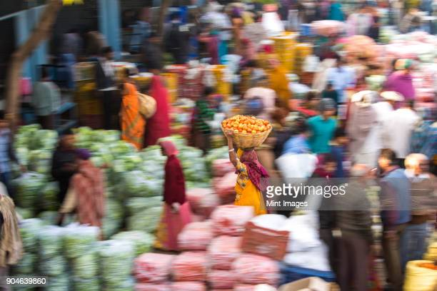 high angle view of fruit and vegetable market, woman carrying a load on her head, motion blur. - india market stock photos and pictures