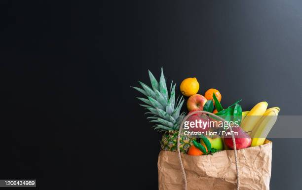 high angle view of fruits in brown paper shopping bag on table against black background - bag stock pictures, royalty-free photos & images