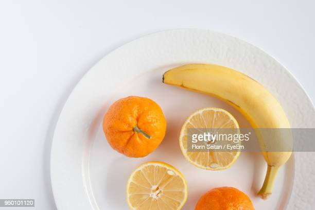 High Angle View Of Fruits In Plate Over White Background