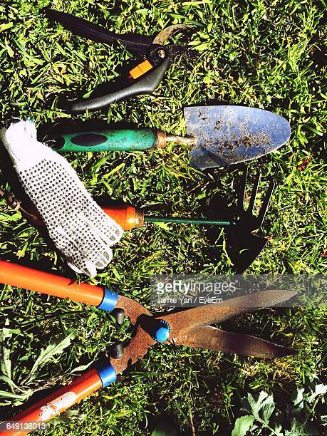 High Angle View Of Gardening Equipment On Grassy Field