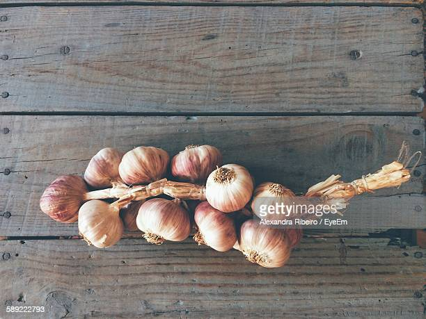 High Angle View Of Garlic Bulbs On Wooden Plank
