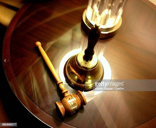 High Angle View Of Gavel And Bell On Wooden Table