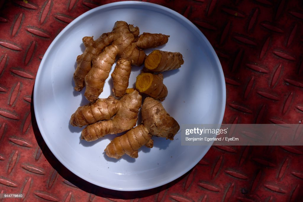 High Angle View Of Ginger In Plate On Red Floor : Stock Photo