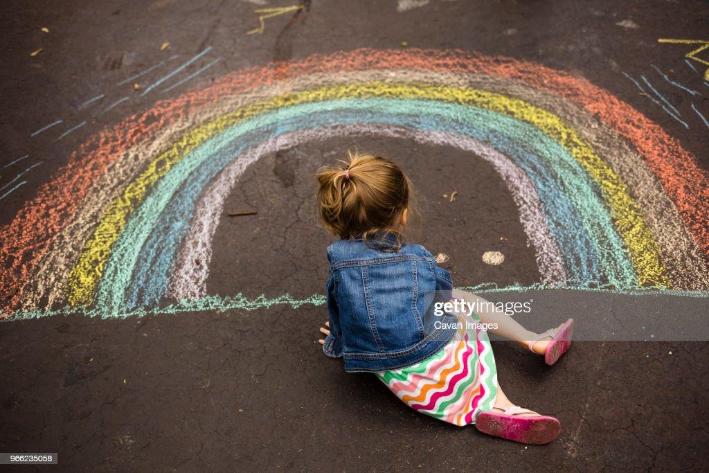 High angle view of girl drawing rainbow on asphalt : Stock Photo