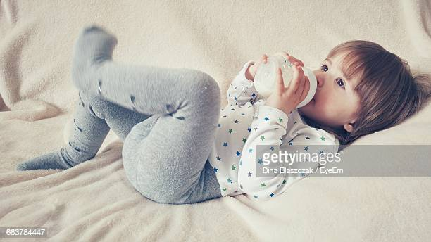 High Angle View Of Girl Drinking Milk From Bottle While Lying On Bed At Home