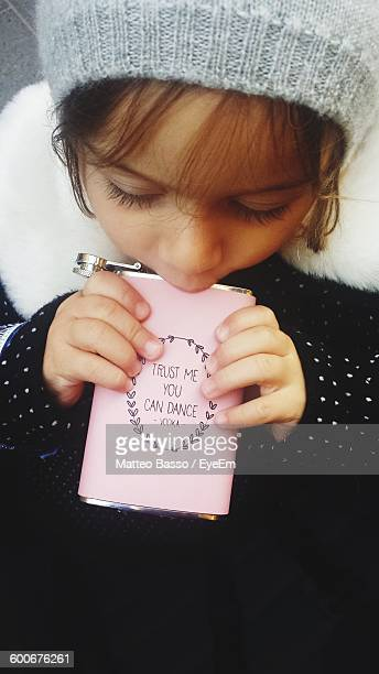 High Angle View Of Girl Drinking Vodka From Flask