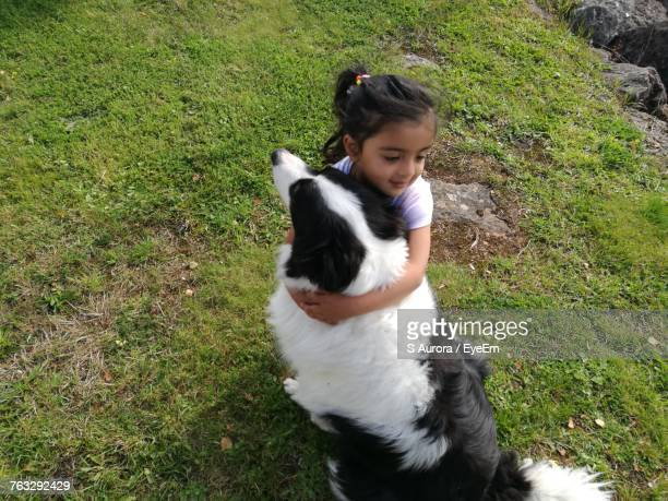 High Angle View Of Girl Embracing Border Collie On Grassy Field