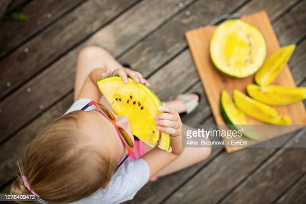 high angle view of girl holding fruit - alina stock pictures, royalty-free photos & images