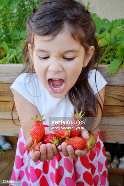 high angle view of girl holding strawberries while standing with mouth open - girls open mouth stock-fotos und bilder