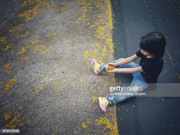 High Angle View Of Girl Holding Yellow Flowers While Sitting On Footpath