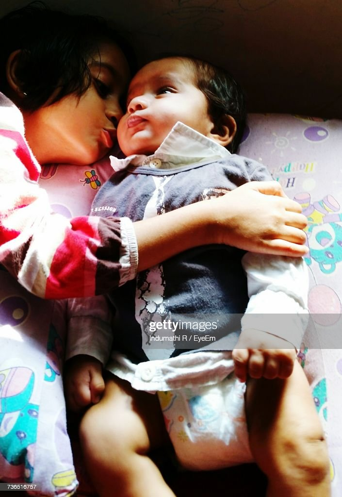 High Angle View Of Girl Kissing Brother Lying On Bed : Stock Photo