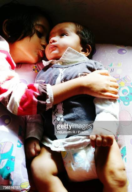 high angle view of girl kissing brother lying on bed - indian girl kissing stock photos and pictures