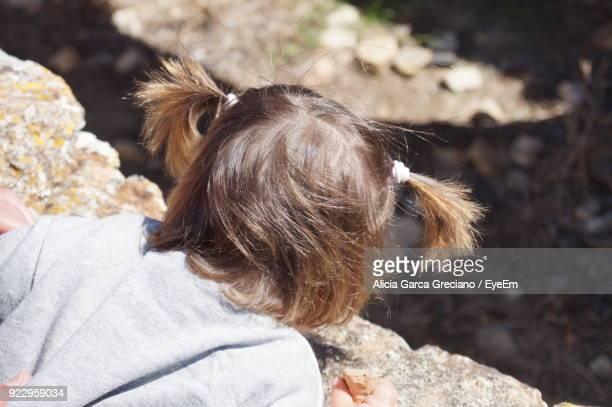 High Angle View Of Girl Leaning On Retaining Wall