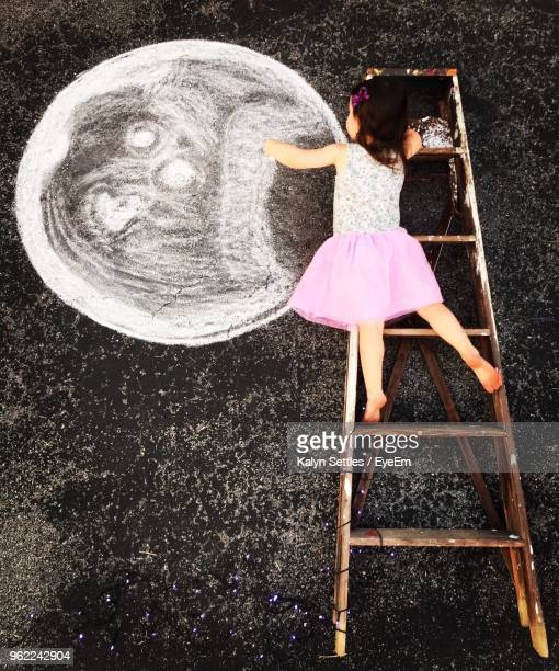 high angle view of girl lying on ladder while making chalk drawing on street - ladder to the moon stock pictures, royalty-free photos & images
