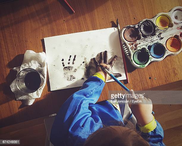 High Angle View Of Girl Painting Hand With Paintbrush On Table