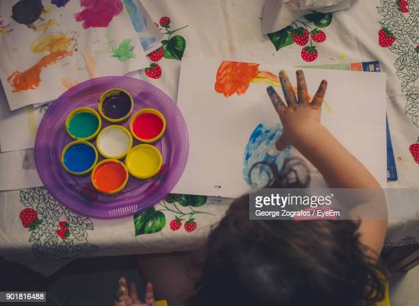 High Angle View Of Girl Painting On Paper At Table