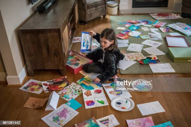high angle view of girl painting on papers while sitting on floor at home - basteln stock-fotos und bilder