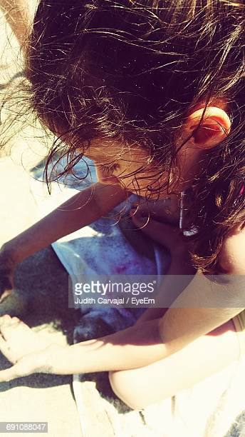 high angle view of girl playing at beach on sunny day - carvajal stock photos and pictures