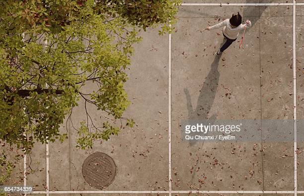 High Angle View Of Girl Playing Badminton At Court