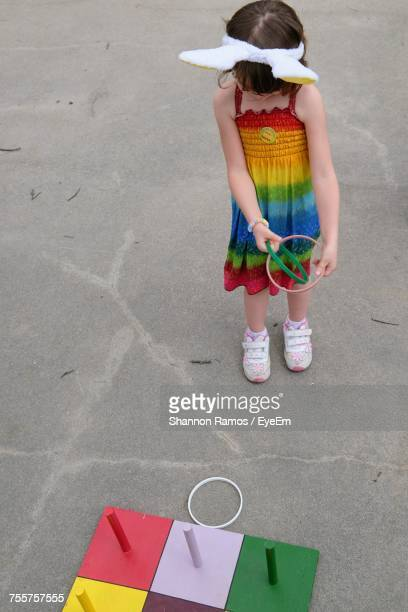 High Angle View Of Girl Playing Ring Toss Game In Playground