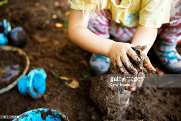 high angle view of girl playing with mud - mud stock pictures, royalty-free photos & images