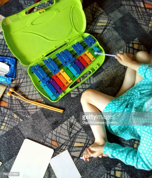 high angle view of girl playing with xylophone at home - girls open legs stock photos and pictures