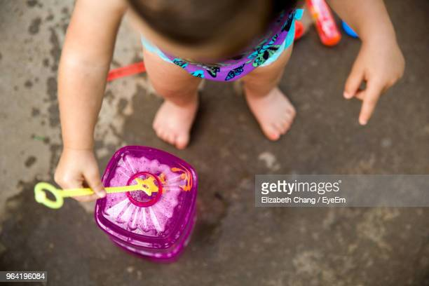 High Angle View Of Girl Plying With Bubble Wand While Standing Outdoors