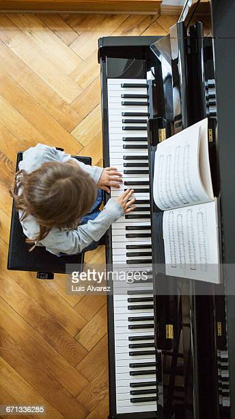 High angle view of girl practicing piano