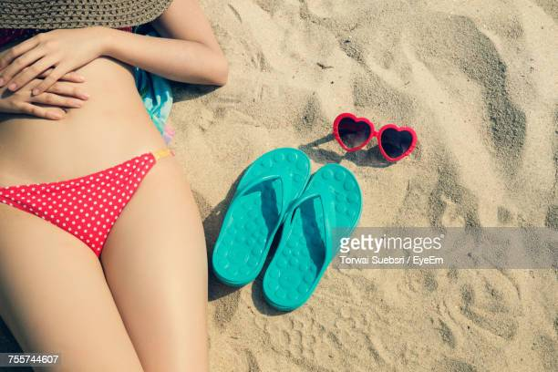 high angle view of girl relaxing on beach - bikini bottom stock pictures, royalty-free photos & images