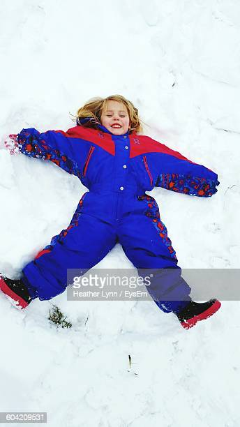 high angle view of girl resting on snow covered field - lynn pleasant stock pictures, royalty-free photos & images
