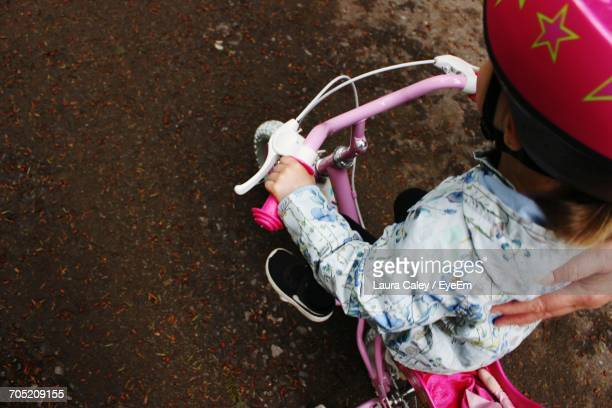 high angle view of girl riding bicycle on street - handlebar stock photos and pictures