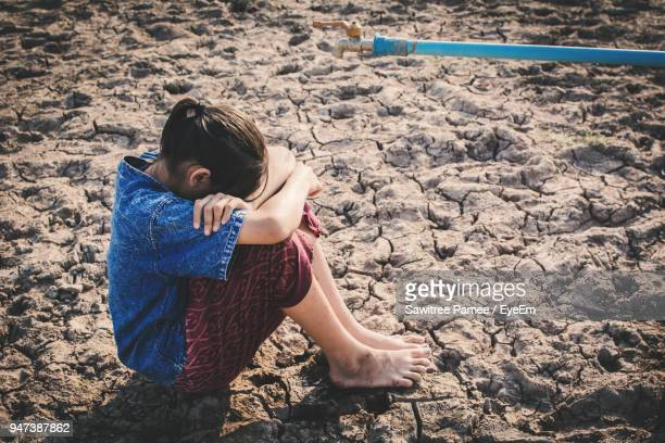 High Angle View Of Girl Sitting On Field By Faucet During Drought