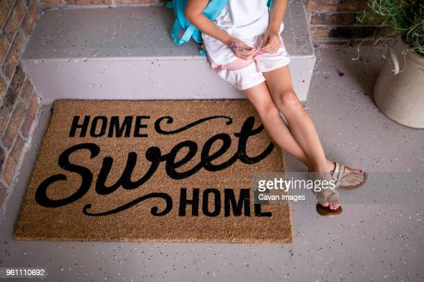 high angle view of girl sitting on retaining wall by doormat - human doormat foto e immagini stock