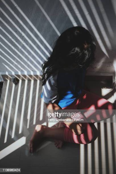 high angle view of girl sitting on wall at home - child abuse stock pictures, royalty-free photos & images