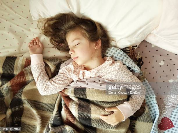 high angle view of girl sleeping on bed - elena knouzi stock pictures, royalty-free photos & images