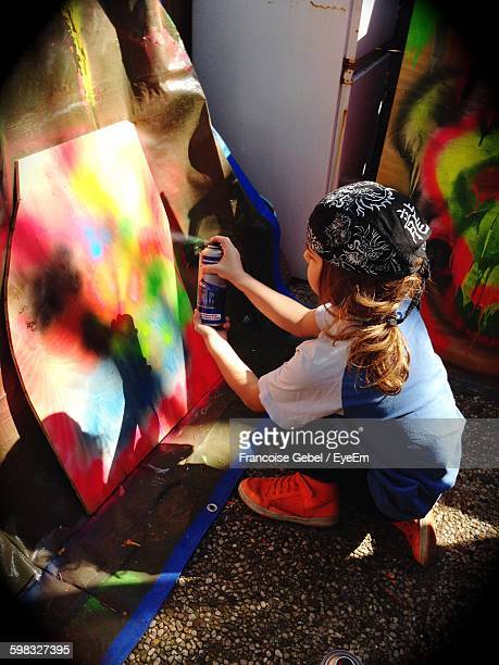 High Angle View Of Girl Spray Painting On Canvas