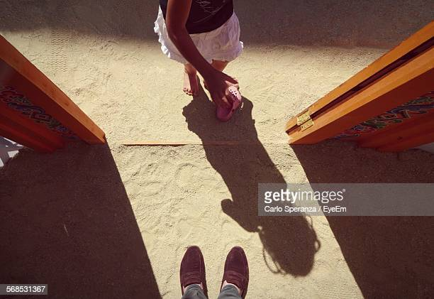 high angle view of girl standing at doorway in sand - girls open legs stock photos and pictures