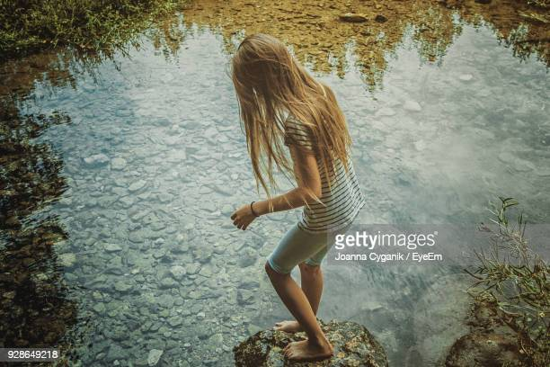 High Angle View Of Girl Standing On Rock By Pond