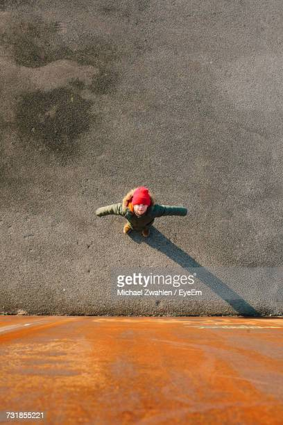 High Angle View Of Girl Standing With Arms Outstretched On Street By Orange Wall
