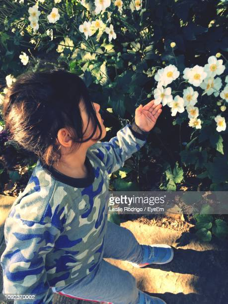 High Angle View Of Girl Touching Flowering Plant