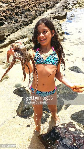 High Angle View Of Girl Wearing Bikini Holding Octopus While Standing On Shore