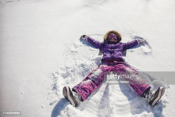 high angle view of girl wearing ski suit lying snow making snow angel - ski wear stock pictures, royalty-free photos & images