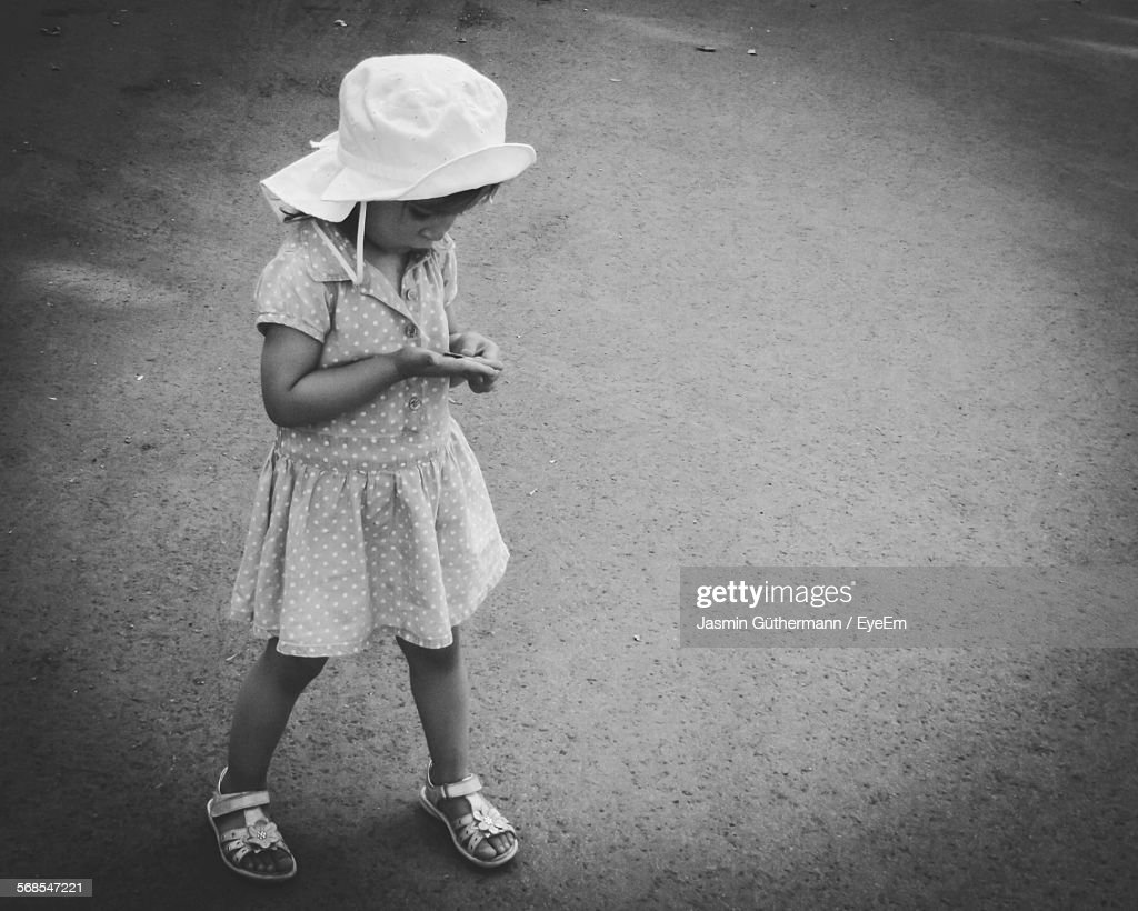 High Angle View Of Girl With Coin Walking On Street : Stock Photo