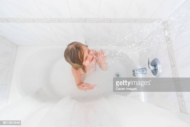 high angle view of girl with eyes closed enjoying shower in bathtub at home - fille sous la douche photos et images de collection