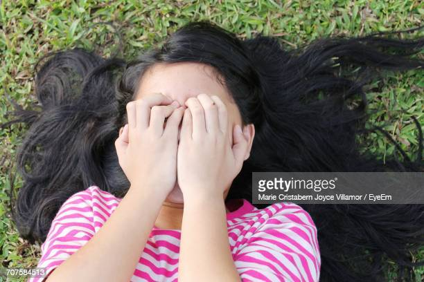 High Angle View Of Girl With Face Covered By Hands While Lying Down On Field