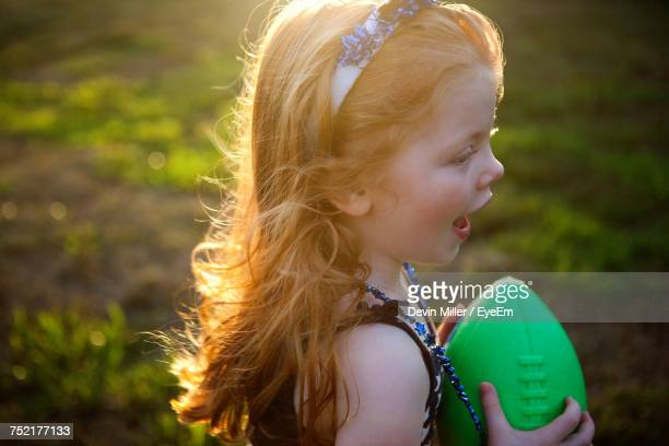 high angle view of girl with mouth open looking away while holding rugby ball - girls open mouth stock-fotos und bilder