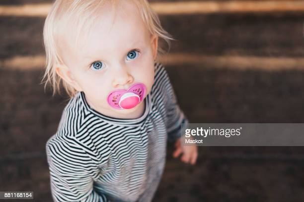 High angle view of girl with pacifier standing outdoors