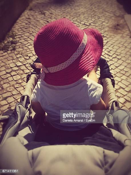High Angle View Of Girl With Pink Hat Sitting In Baby Stroller
