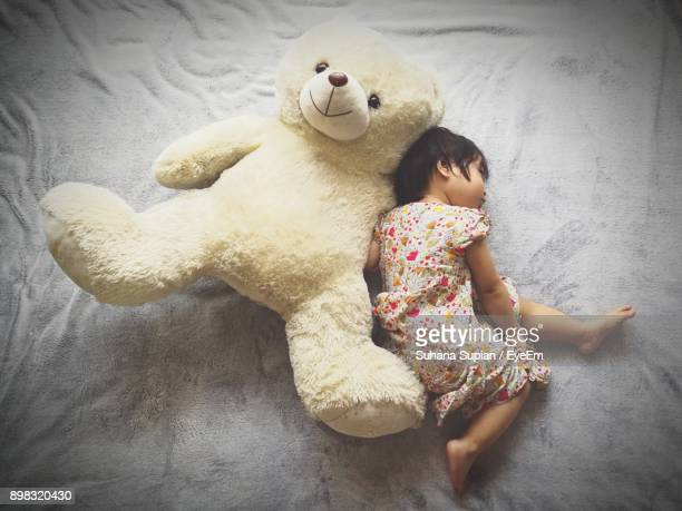 High Angle View Of Girl With Teddy Bear Lying Down On Bed