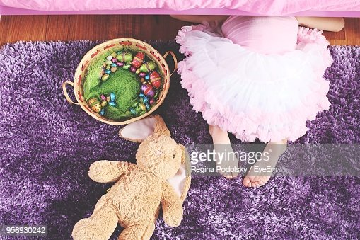 High Angle View Of Girl With Toys On Rug At Home